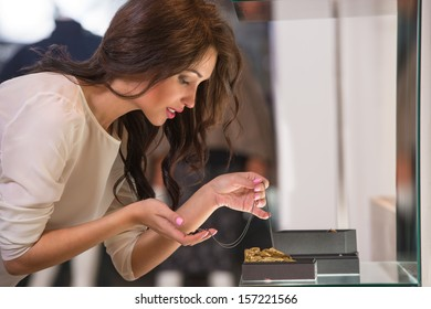 Young woman looking at the shop showcase and taking jewelry to look at it closer