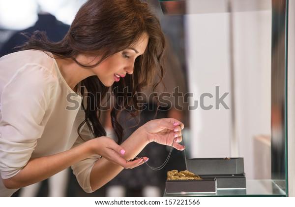 ショーケースを見て、近くを見るために宝石を手に入れる若い女性
