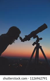 Young woman looking at the sky with astronomical telescope.