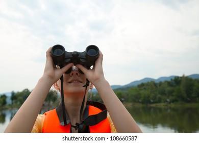 Young woman looking to sky through binoculars