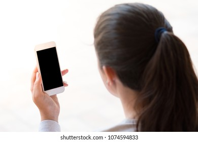 young woman looking at the smartphone, isolated on white background