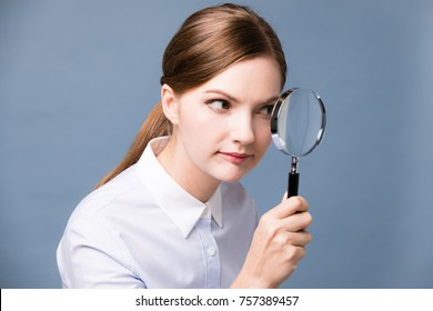 Young woman looking at something with magnifying glass.