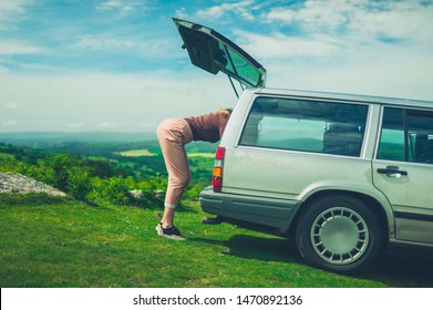 A young woman is looking for something in the trunk of her car in nature on a sunny summer day