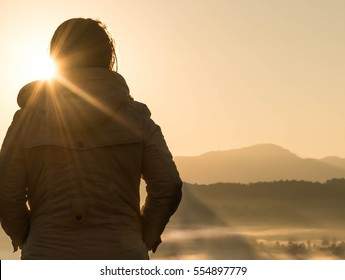 A young woman is looking at the Sun rise over the mountain.