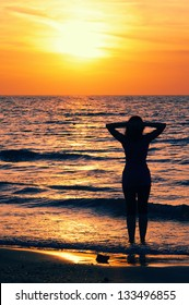 Young woman is looking at sunset