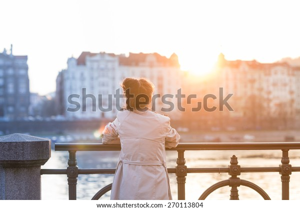 A young woman is looking at the sunset over a river in the city Prague with the old buildings in the background. Soft spring backlit. Color toned image.