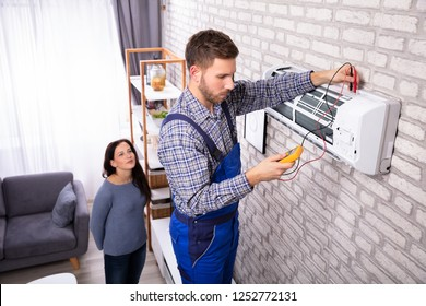 Young Woman Looking At Technician Examining Air Conditioner With Digital Multimeter