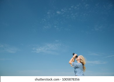 Young woman looking through binoculars with the sky on background
