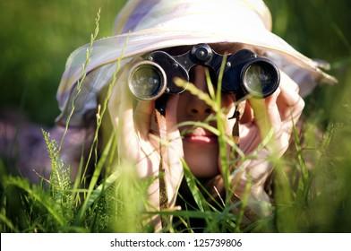 Young woman looking through binoculars in grass