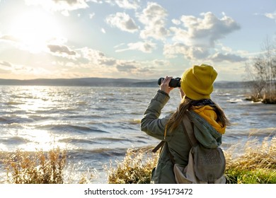 Young woman looking through binoculars at birds on the lake. Birdwatching, zoology, ecology. Research in nature, observation of animals. Ornithology