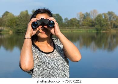 Young woman looking through binoculars at lake