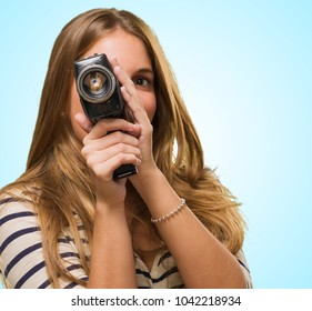 Young Woman Looking Through A Camera against a blue background