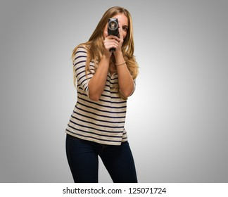 Young Woman Looking Through A Camera against a grey background