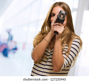 Young Woman Looking Through A Camera against an abstract background