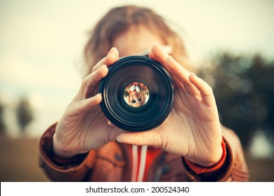 Young woman looking through camera lens