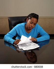 A young woman looking through paperwork.