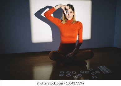 Young woman looking through photo slide in front of projector screen