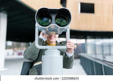 Young woman looking through sightseeing binoculars