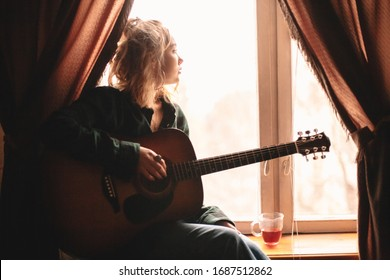 Joven mirando por la ventana mientras se sienta en la ventana con guitarra en casa