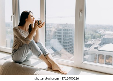 Young woman looking through the window with a city view, sitting on a windowsill, enjoying coffee or tea in the morning. - Shutterstock ID 1718400526