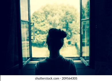 Young woman looking through the window on the garden or forest in the countryside. Vintage filter. Blue tone.
