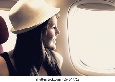 Young woman is looking through a window in the aircraft. Pastel colors