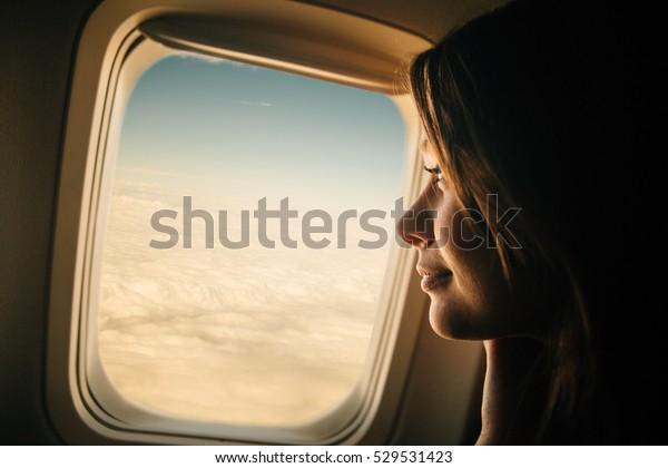 Junge Frau, die durch das Fenster im Flugzeug schaut