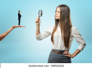 Young woman looking at a tiny man with a magnifying glass while he is standing on another woman hand. Looking for an employee. Applying for a job. Considering candidates for posts.