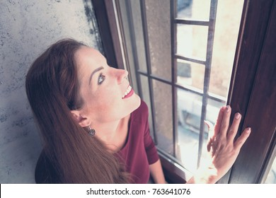 Young woman looking and touching window. Top view