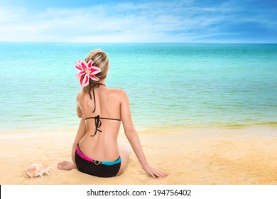 Young woman looking at tropical sea. Rear view outdoor