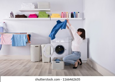 Young Woman Looking At T-shirt In Front Of Open Washing Machine