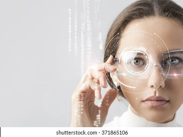 Young woman looking at virtual graphics in futuristic background