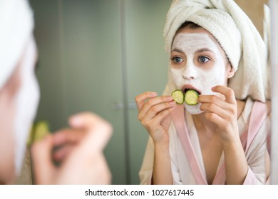 Young woman looks after the face makes a mask in the bathroom