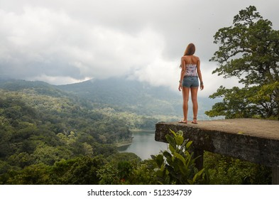 Young woman looks at the bratan lake on bali, indonesia