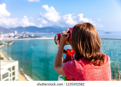A young woman looks at the city through the tower viewer. Nha Trang, Vietnam.
