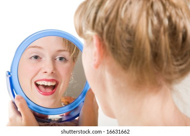 The young woman looks at itself in a mirror