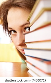 The young woman looks out from for piles of books. A close up