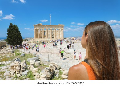 Young woman looks at Parthenon on the Acropolis of Athens, Greece. The famous ancient Greek Parthenon is the main tourist attraction of Athens. Girl traveler visits the Parthenon at the top of hill.