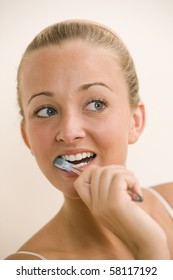 A young woman looks to the side while brushing her teeth.  Vertical shot.