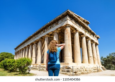 Young woman looks at Temple of Hephaestus, Athens, Greece. This ancient Greek structure is one of main landmarks of Athens. Tourist visits the Agora in Athens centre. Adult girl travels across Greece.