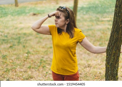 Young woman lost in the forest looking in the distance for a way out - Casually dressed girl with brown hair holding one hand against her head walking in the forest alone