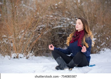 Young woman in lotus pose in the snow