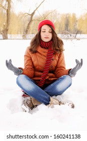 young woman in a lotus position on the snow