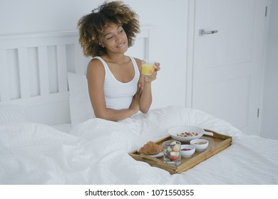 Young woman lounging in bed having fresh juice and delicious breakfast served on tray while looking away and daydreaming.