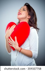 Young woman in love clutching a red heart with a smile of pleasure as she romanticises about her Valentines sweetheart, over grey