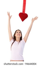 Young woman in love, jumping to reach red heart at valentines day.?