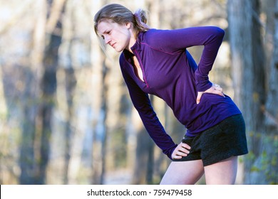 Young woman with lower back pain while running exercising on nature trail outdoors