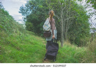 A young woman with luggage is walking in the countryside