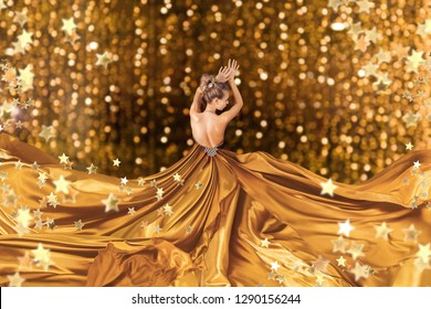 Young woman in luxurious long golden dress. Rear wiew to girl in fluttering gown