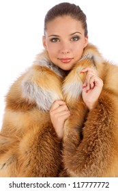 Young woman in luxury fur coat isolated on white background